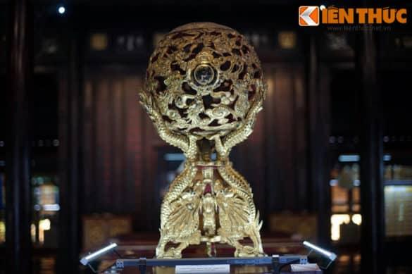 Quả cầu cửu long sơn thếp, một món đồ nội thất độc đáo từng được bày trong cung vua nhà Nguyễn. Hiện vật này được tạo hình chín con rồng vờn quanh ngọc châu, làm bằng gỗ quý thếp vàng toàn bộ bề mặt theo kỹ thuật truyền thống.