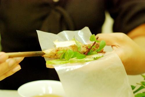 Nem lụi được cuốn bởi bánh tráng và ăn kèm nhiều loại rau.