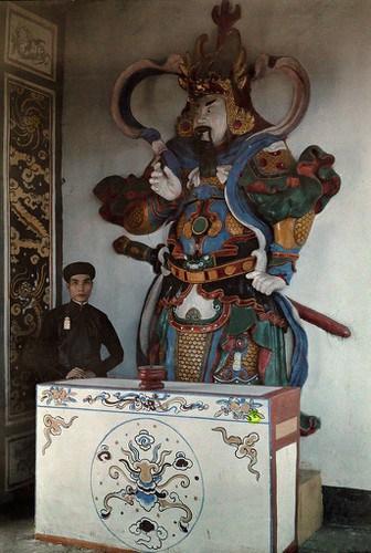 Viên quan trẻ của triều đình Huế đứng bên tượng hộ pháp ở chùa Thiên Mụ, 1931. Ảnh: W. Robert Moore.