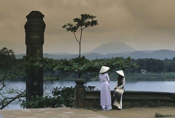 Hai thiếu nữ ngồi ở sân chùa Thiên Mụ, hậu cảnh là sông Hương, thập niên 1970.