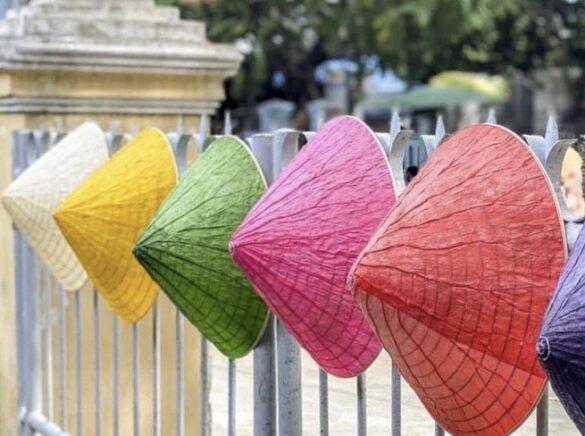 Hoạ sỹ Nguyễn Thanh Thảo tạo ra những chiếc nón lá sen 'xuyên sáng' với 5 sắc màu. (Ảnh: Mai Trang/TTXVN)